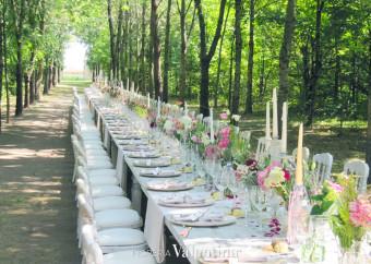 Una tavolata imperiale tra lisianthus bianchi, rosa, bacche in toni pastello e il verde trionfale della natura
